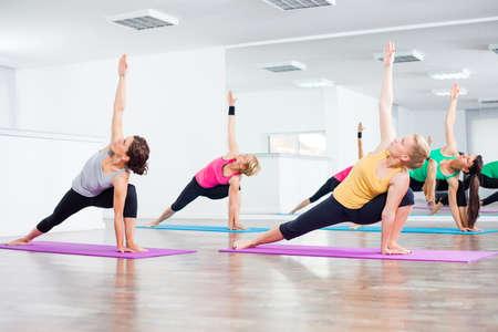 Four girls practicing yoga, Virabhadrasana Rotated warrior pose Фото со стока