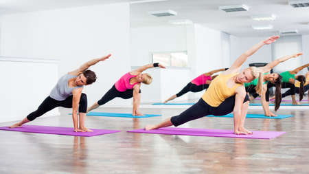 Four girls practicing yoga, Vasisthasana Half side plank pose