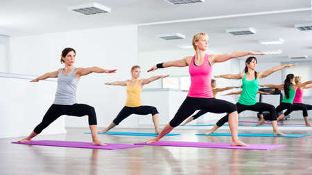Four girls practicing yoga, Yoga - Virabhadrasana Warrior pose