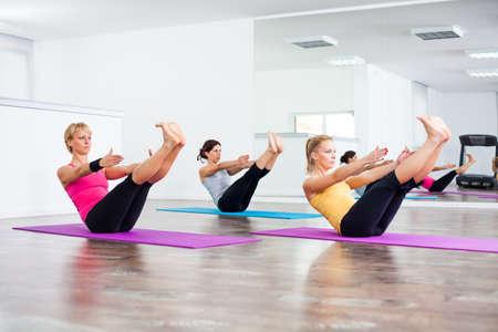 Drei Mädchen praktizieren Yoga, Pose Yoga Navasana Boat Standard-Bild - 44960028