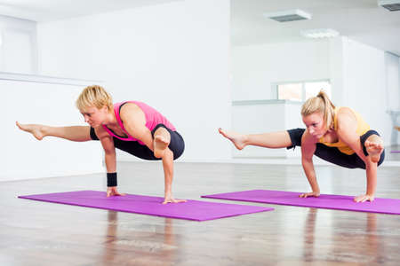 firefly: Two girls practicing yoga, TittibhasanaInsect or Firefly Pose Stock Photo