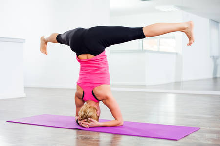 supported: Girl practicing yoga, Sirsasana Supported Headstand Stock Photo
