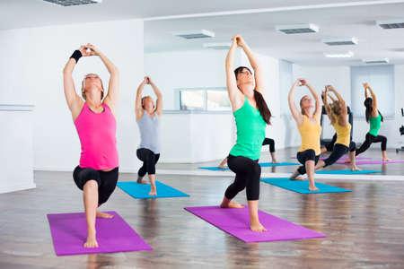warrior pose: Four girls practicing yoga, Yoga-Virabhadrasana Warrior pose