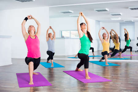 Four girls practicing yoga, Yoga-Virabhadrasana Warrior pose