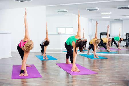 trikonasana: Four girls practicing yoga, Yoga Trikonasana Bikram triangle right pose
