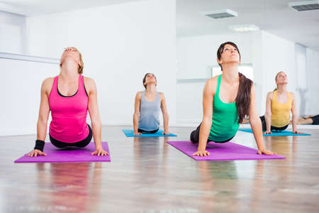 Four girls practicing yoga, Yoga - Bhujangasana Cobra Pose