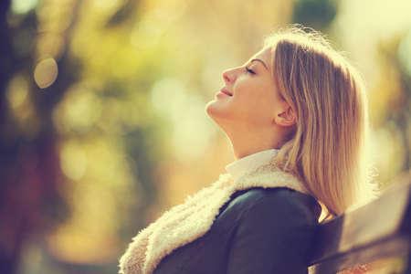 秋に新鮮な空気を楽しんで幸せな女性は意図的にトーンダウン。 写真素材