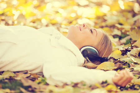 Young happy woman listening music in park, intentionally toned.