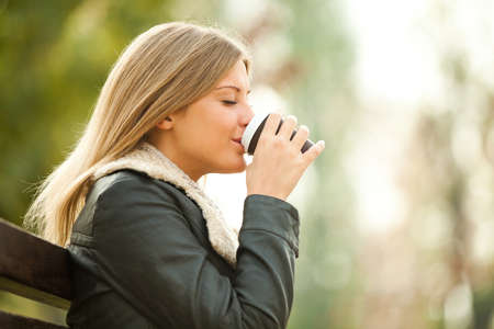 Young woman drinking coffee to go