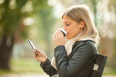 women holding cup: Young woman using tablet in park, drinking coffee to go