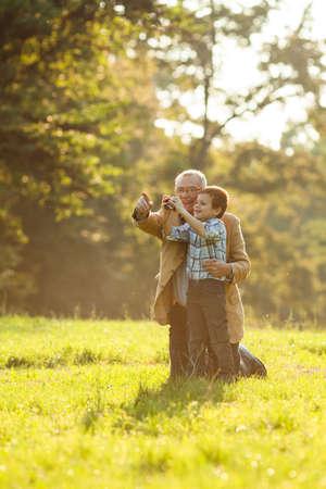 grandfather: Abuelo y nieto fotografiar naturaleza en el parque Foto de archivo