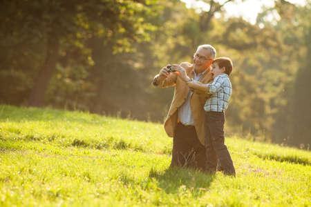 Семья: Дед и внук фотографирования природы в парке Фото со стока