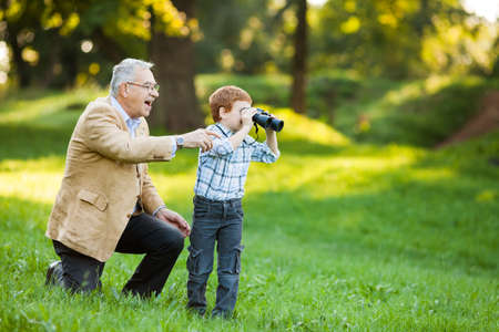 active people: Grandfather and grandson watching nature with binoculars in park