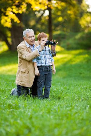 祖父と孫の公園で双眼鏡を使って自然を見て