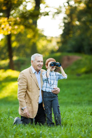 green man: Grandfather and grandson watching nature with binoculars in park