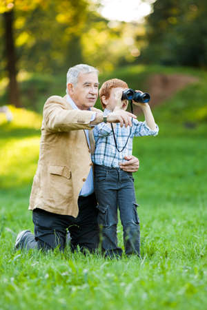 active seniors: Grandfather and grandson watching nature with binoculars in park