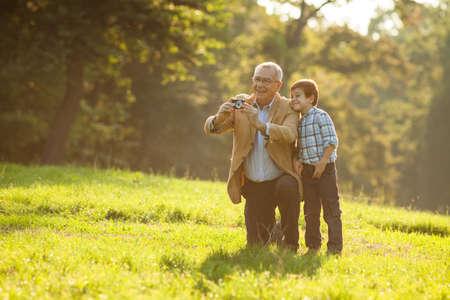 Grootvader en kleinzoon fotograferen van de natuur in het park