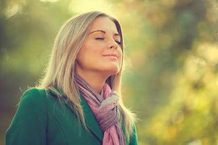 aire puro: Mujer joven que goza de aire fresco en el otoño, entonado intencionalmente.