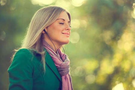 listening: Young woman enjoying fresh air and listening music in autumn, intentionally toned. Stock Photo