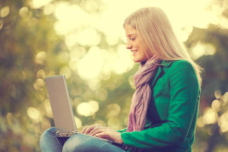 surfing the net: Happy woman using laptop in park, intentionally toned. Stock Photo
