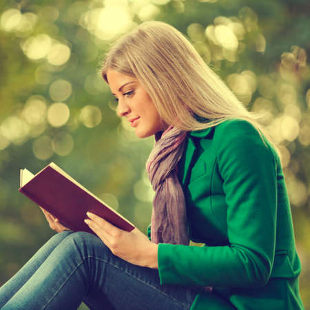 intentionally: Young woman reading book in park, intentionally toned.