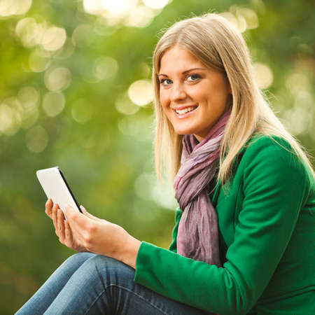 surfing the net: Happy woman using digital tablet in park