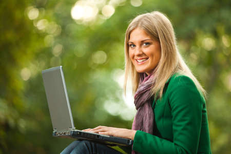 surfing the net: Happy woman using laptop in park