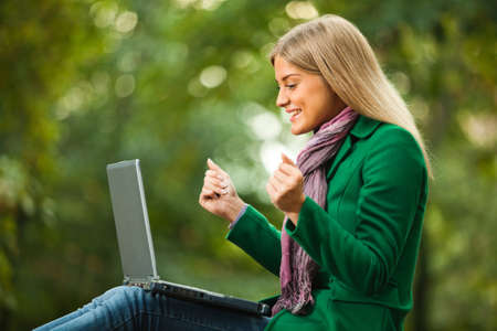 Happy woman using laptop in park Фото со стока - 45944640