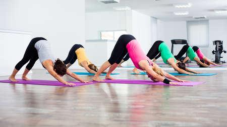 classes: Four girls practicing yoga, Yoga-Shashankasana - Hare pose