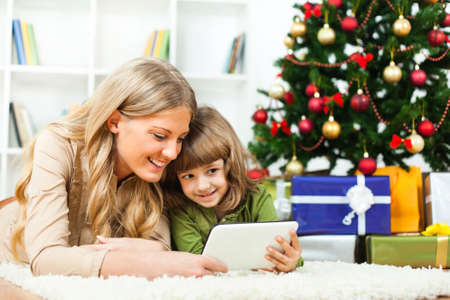 surfing the net: Happy mother and daughter with new years tree and gift boxes, lying on floor and using tablet