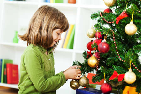 decorating christmas tree: Little girl decorating christmas tree