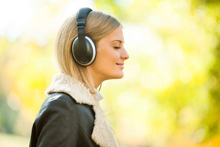 Young happy woman listening music in park