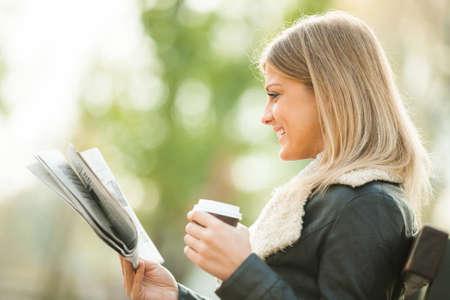 periodicos: Periódico lectura de la mujer joven y el consumo de café para ir Foto de archivo