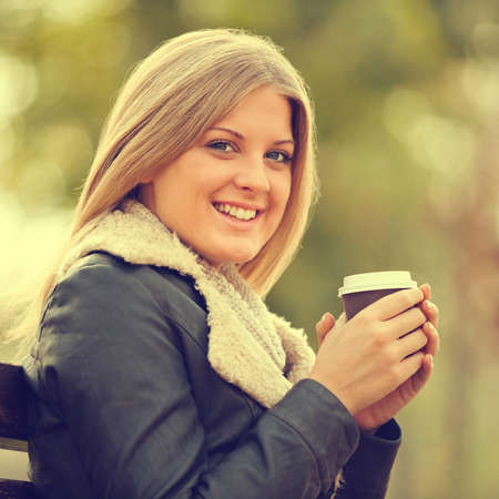 intentionally: Young woman drinking coffee to go in park, intentionally toned.