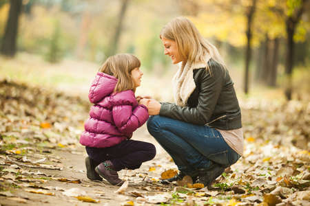 holding mother's hand: Happy mother and daughter having fun in park in autumn Stock Photo