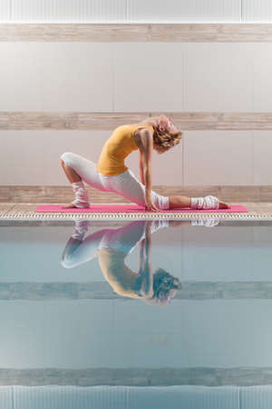 virabhadrasana: Young woman practicing yoga at swimming pool, Virabhadrasana, variation of Warrior pose Stock Photo