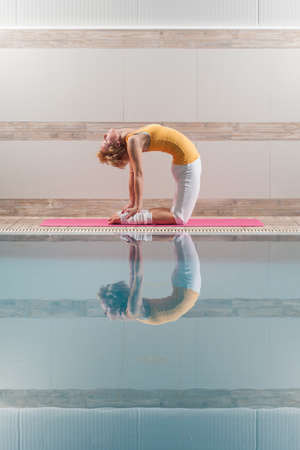 ushtrasana: Young woman practicing yoga at swimming pool, Ushtrasana Camel pose