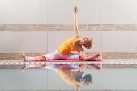 konasana: Young woman practicing yoga at swimming pool, Upavistha Konasana Revolved Seated Angle Pose