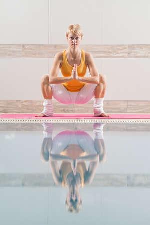 buddhist stupa: Young woman practicing yoga at swimming pool, Buddhist stupa pose Stock Photo