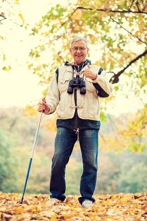 intentionally: Senior man hiking in forest, intentionally toned image.