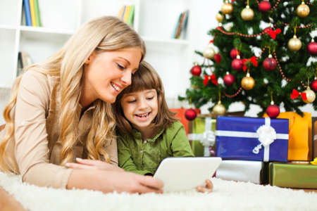 new year's day: Happy mother and daughter with new years tree and gift boxes, lying on floor and using tablet