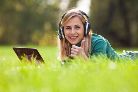 people looking up: Young woman is using digital tablet and listening music in park Stock Photo