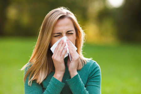 symptom: Woman with allergy symptom blowing nose Stock Photo