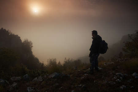 mountains and sky: Man standing above the misty canyon early in the morning