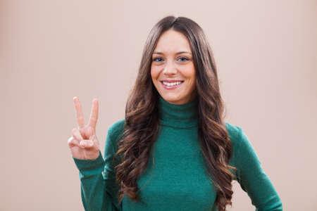 simbolo della pace: Ritratto di giovane donna felice che sta mostrando il segno di pace
