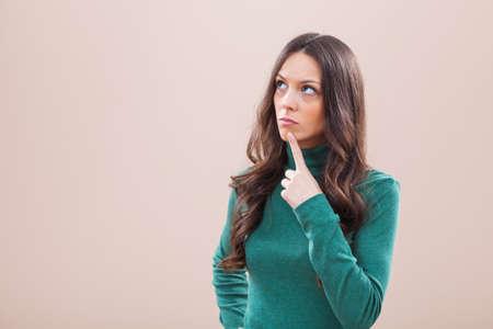 Studio portrait of young pensive woman