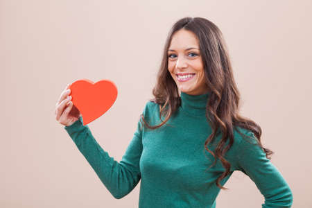 ragazza innamorata: Portrait of young happy woman who is holding red heart shaped box