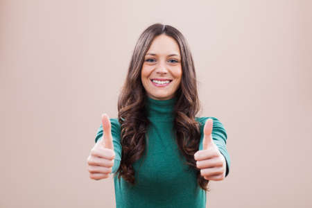 look up: Portrait of young woman who is smiling and showing thumb up Stock Photo