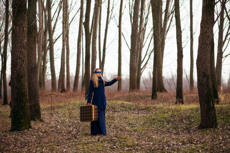 blindly: Woman with blindfold walking in forest with old suitcase and looking for a way to go
