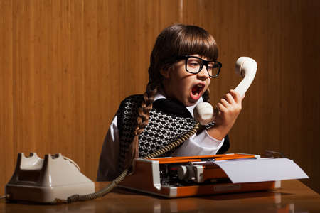 angry women: Angry little girl shouting on phone in her office Stock Photo